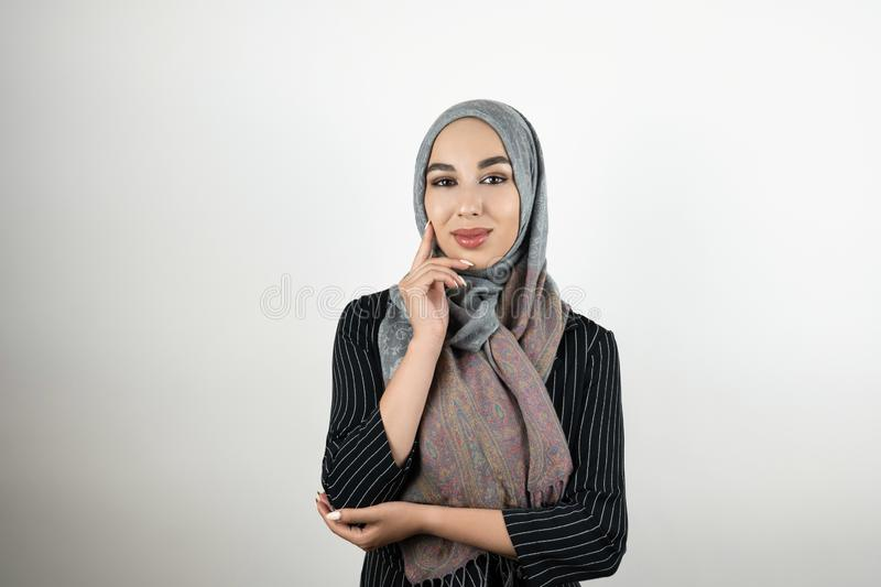 Young beautiful Muslim business woman wearing turban hijab headscarf touching her face with one hand in standing royalty free stock photo