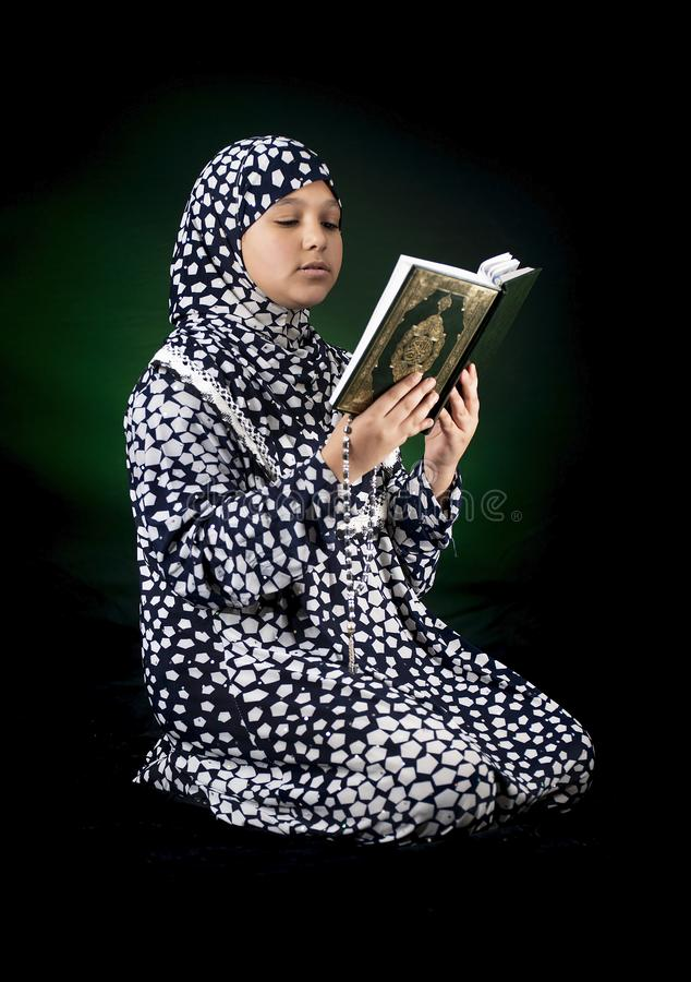 Young Beautiful Muslim Girl Reading The Holy Book of Quran stock photo
