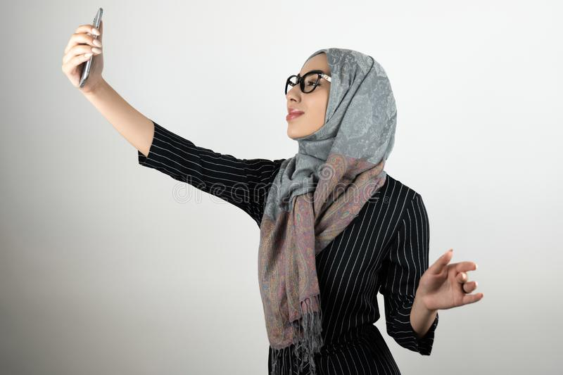 Young beautiful Muslim woman in glasses wearing turban hijab, headscarf holding smartphone shooting a selfie isolated royalty free stock photo
