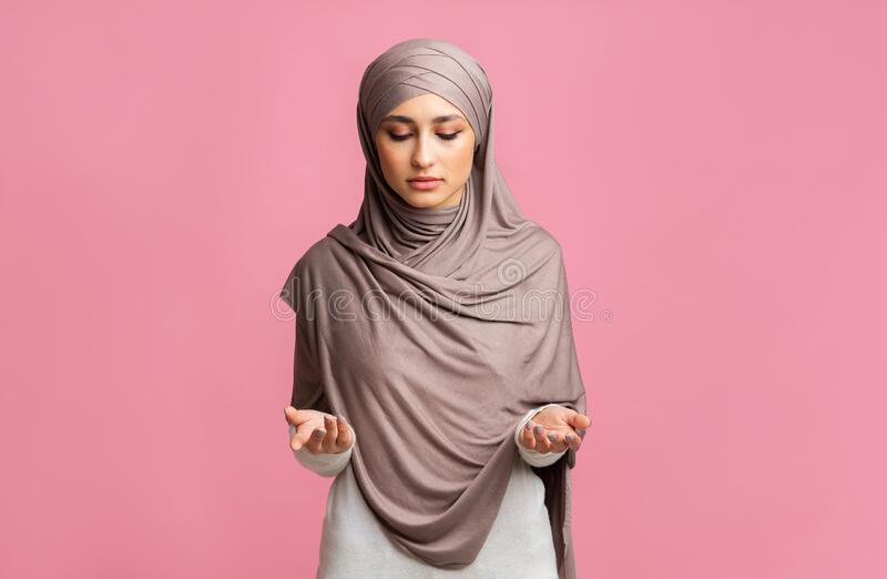 Young beautiful muslim woman in headscarf praying over pink background stock image