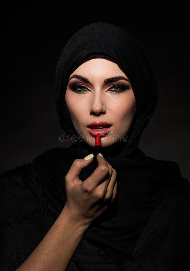 Muslim woman putting lipstick stock image