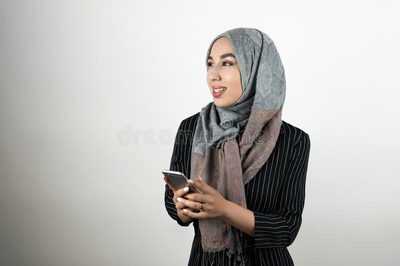 Young beautiful Muslim woman wearing turban hijab headscarf holding smartphone in her hands isolated white background royalty free stock photos