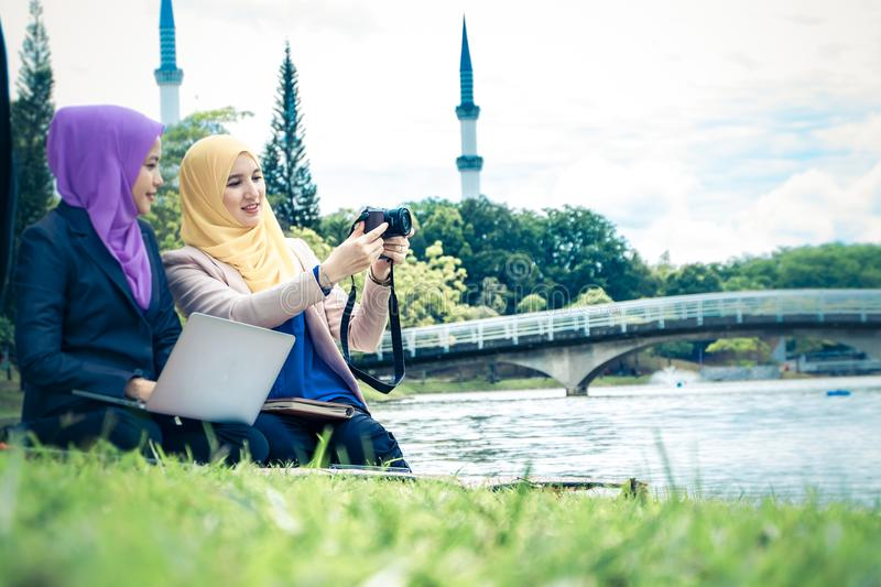Enjoying friendship and discuss photograph they shoot together. Young beautiful muslimah lifestyle enjoying friendship and discuss photograph they shoot together stock photos