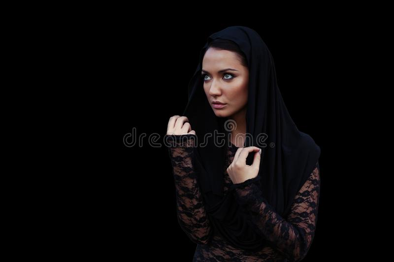 Young beautiful woman with a black hair in the black hood and blouse at the black background stock photography