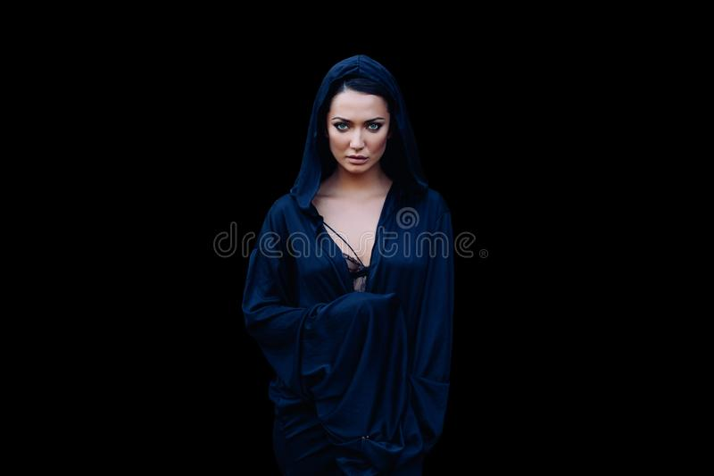 Young beautiful woman with a black hair and in the dark blue cloak with hood at the black background royalty free stock photos