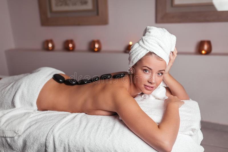 Young beautiful naked woman lying with black stones on her back in spa center. Close up side view photo.wellness, wellbeing royalty free stock photo