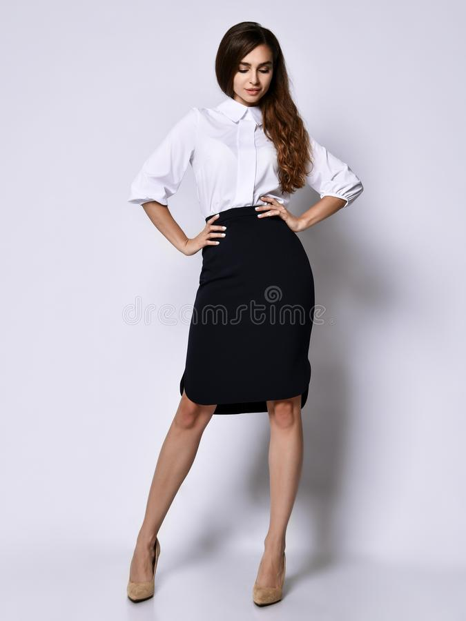 Beautiful woman office manager posing in a new casual white blouse and classic straight dark skirt. Young beautiful office manager posing in a new casual white stock photography