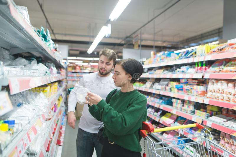 A young, beautiful pair of buyers selects plastic dishes in a supermarket. The choice of goods in the store royalty free stock photo