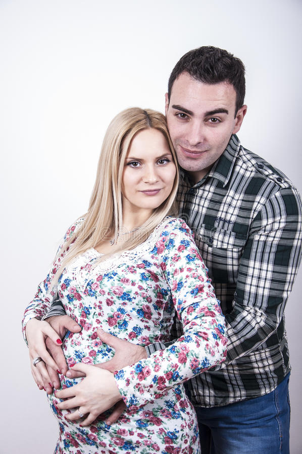 Young beautiful parents. Enjoying, photographed in studio on white background royalty free stock photo