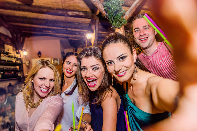 Young beautiful people with cocktails in bar taking selfie. Young beautiful people with cocktails in bar or club taking selfie, having fun stock images