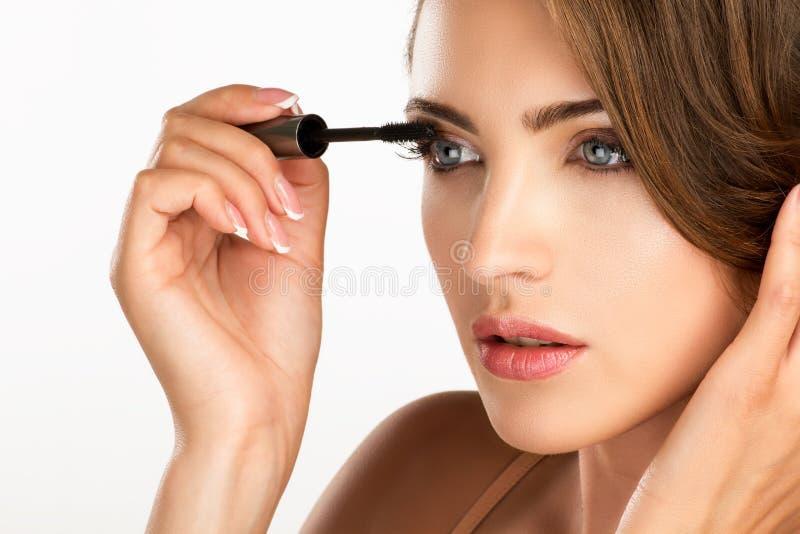 Young beautiful perfect model applying professional mascara stock image