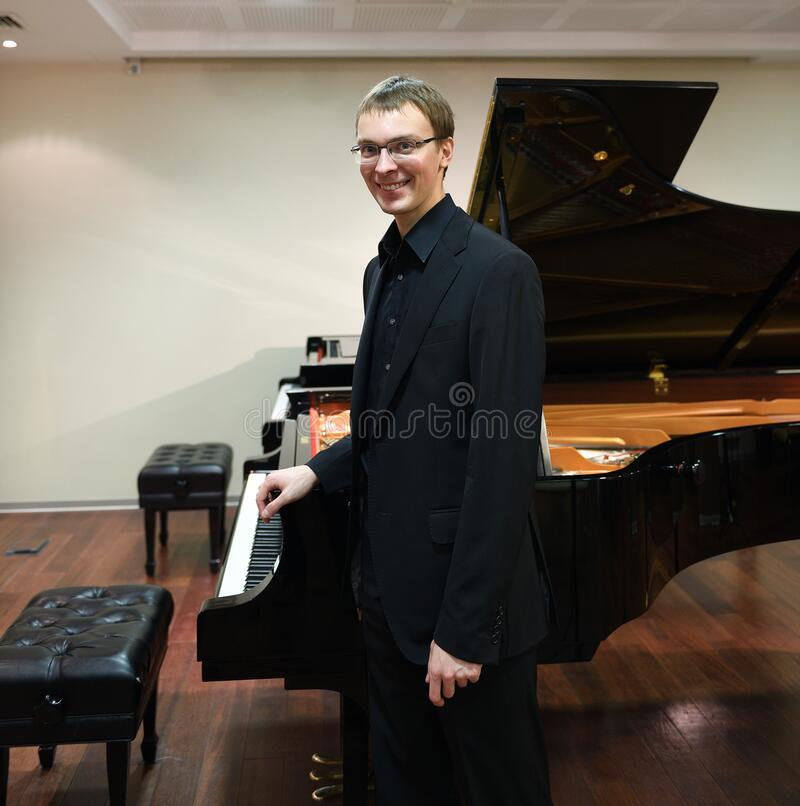 Young beautiful pianist in black suit near Grand piano.  royalty free stock photo