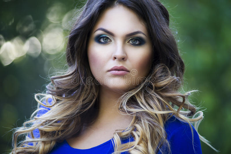 Young beautiful plus size model in blue dress outdoors, confident woman on nature, professional makeup and hairstyle, close-up royalty free stock photography