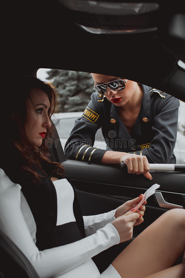 Young beautiful police woman stops car for checking driver. Young beautiful police women stops car for checking driver license royalty free stock image
