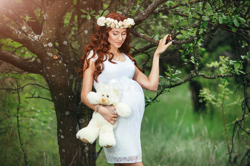 Young beautiful pregnant girl with long brown hair in white dress with toy bear. Young beautiful pregnant girl with long brown hair in white dress with flower royalty free stock photos
