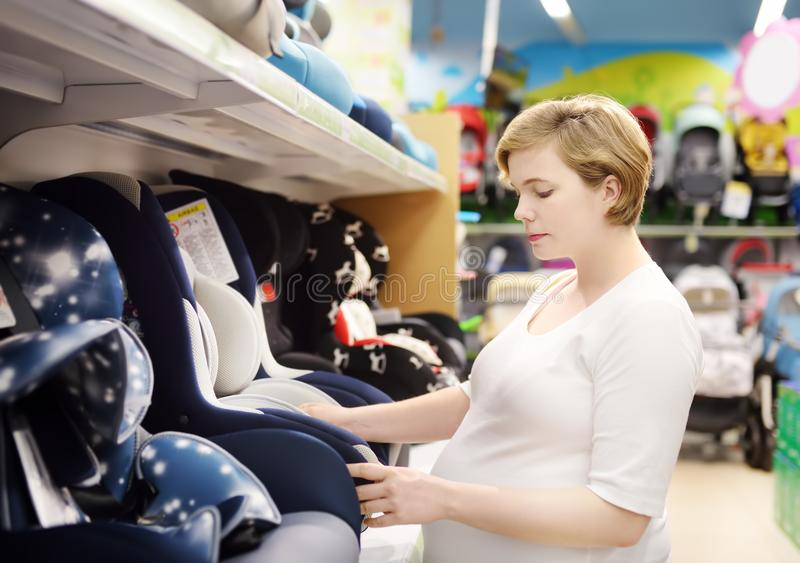 Young beautiful pregnant woman choosing infant car seat. Shopping for expectant mothers and baby stock photos
