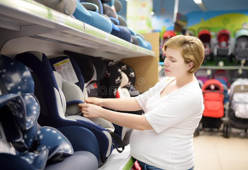 Young beautiful pregnant woman choosing infant car seat. Shopping for expectant mothers and baby royalty free stock photos