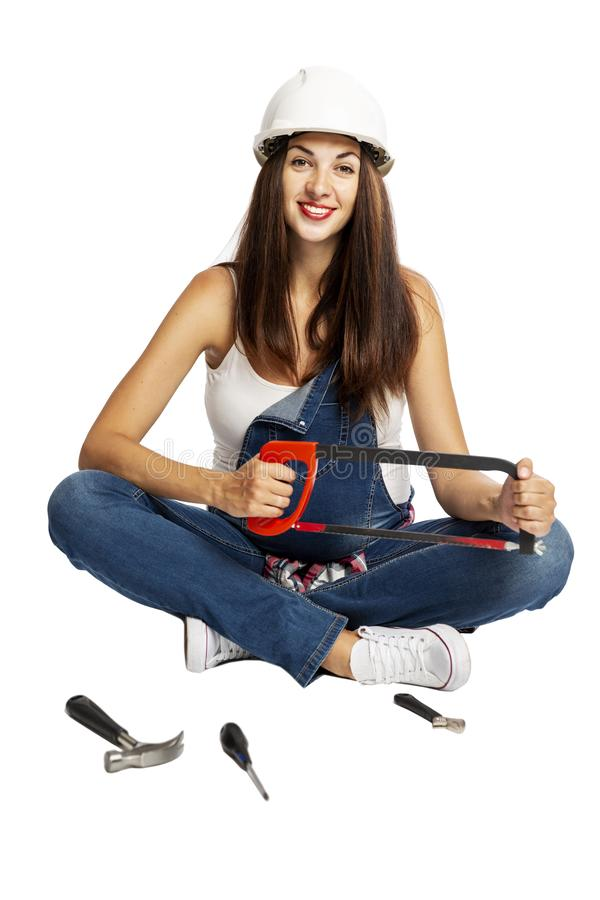 A young beautiful pregnant woman in a construction helmet is sitting on the floor with tools laid out nearby and smiling. royalty free stock photo