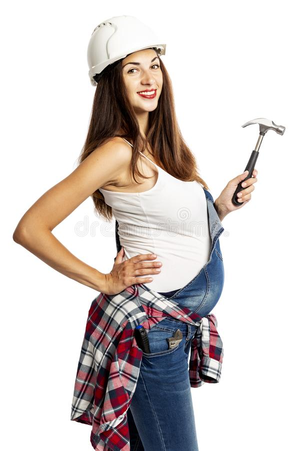 Young beautiful pregnant woman in a helmet with a hammer in her hand. Isolated on a white background. stock photography