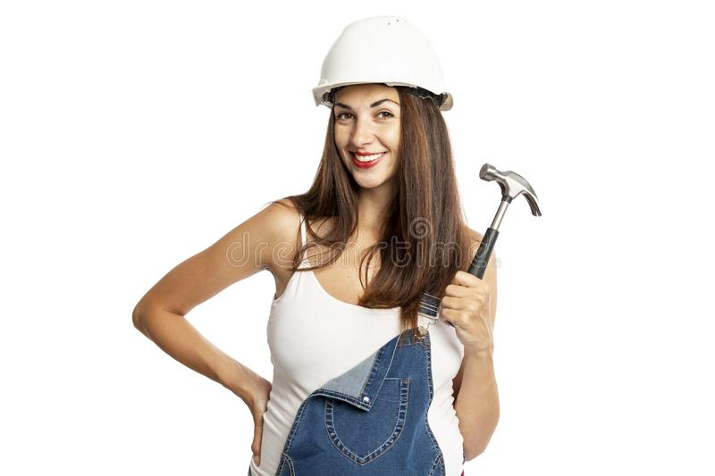 Young beautiful pregnant woman in a helmet with a hammer in her hand. Isolated on a white background royalty free stock photos