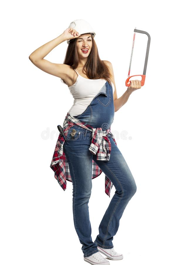 Young beautiful pregnant woman in jeans and construction helmet smiling. In the hands of a construction tool. stock photo