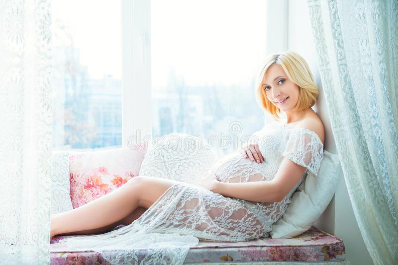 Young beautiful pregnant woman sitting on windowsill at home royalty free stock image