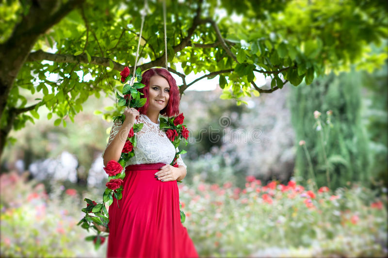 Young beautiful pregnant woman in a swing decorated with red roses royalty free stock photo
