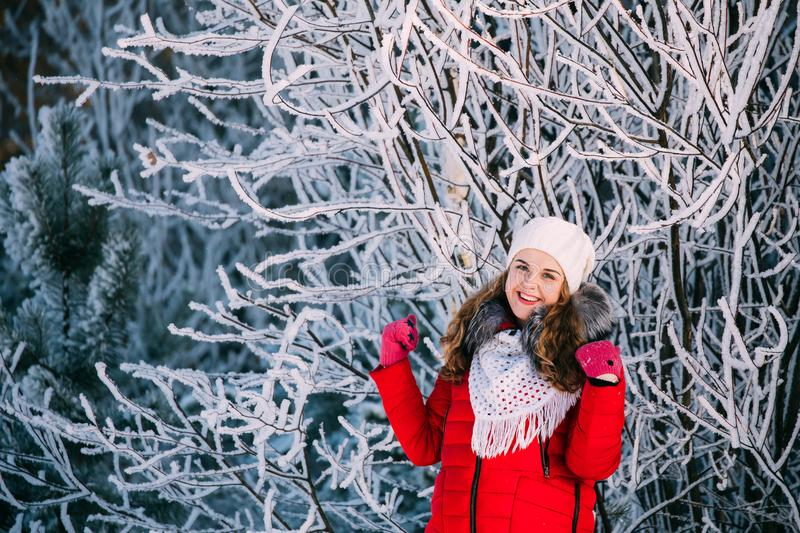 Young Beautiful Pretty Caucasian Girl Woman Dressed In Red Jacke. T And White Hat Smiling In Snowy Forest In Winter Day royalty free stock images