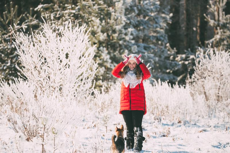 Young Beautiful Pretty Caucasian Girl Woman Dressed In Red Jacket. And White Hat Playing Wiht Puppy Of Mixed Breed Dog In Snowy Forest In Winter Day royalty free stock photography