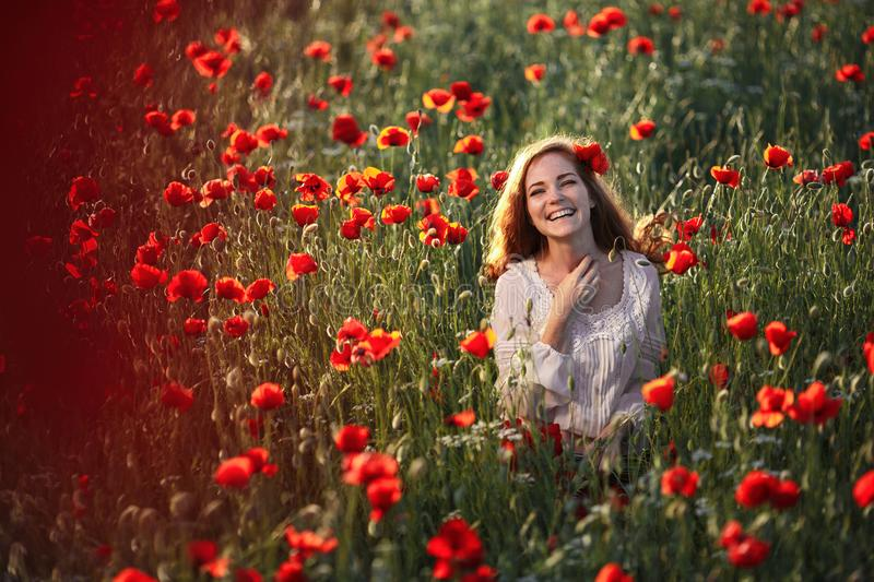 Young beautiful woman in a poppy field stock photo