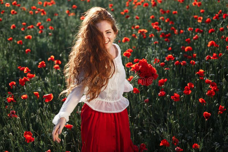 Young beautiful woman walking and dancing through a poppy field at sunset royalty free stock images