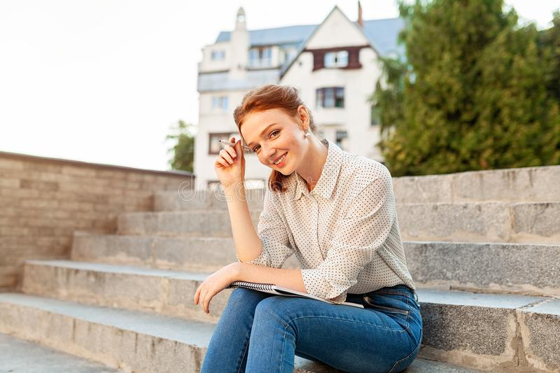 Young beautiful red hair girl with freckles sitting on a stairs near the university writing in a notebook with homework. Portrait of a student. Back to school stock images