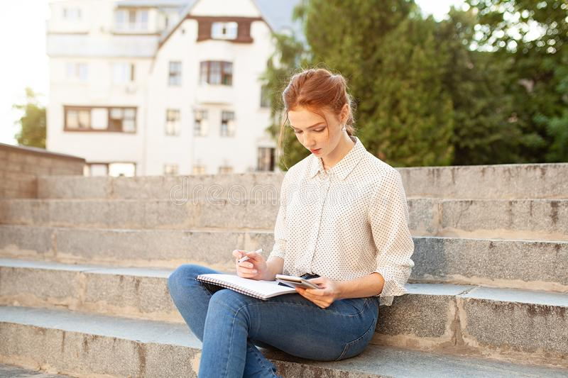Young beautiful red hair girl with freckles sitting on a stairs near the university writing in a notebook with homework. Portrait of a student. Back to school royalty free stock image