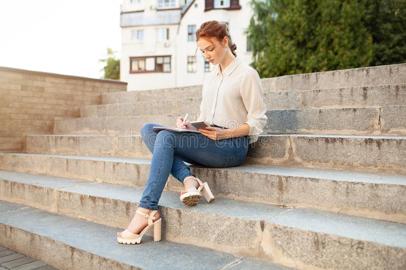 Young beautiful red hair girl with freckles sitting on a stairs near the university writing in a notebook with homework. Portrait of a student. Back to school royalty free stock photo