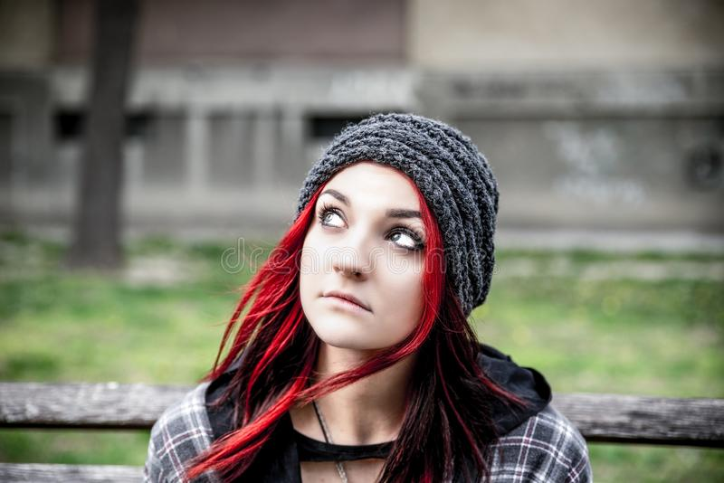 Homeless girl, Young red hair girl sitting alone outdoors with hat and shirt anxious and depressed after she became a homeless. Young beautiful red hair girl royalty free stock photography