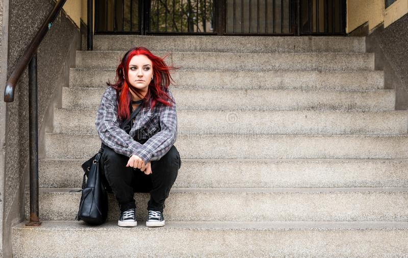 Young beautiful red hair girl sitting alone outdoors on the stairs of the building with hat and shirt feeling anxious and depresse. D after she became a homeless stock images