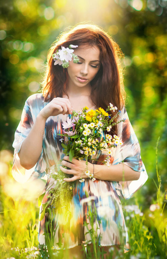 Young beautiful red hair woman holding a wild flowers bouquet in a sunny day. Portrait of attractive long hair female with flowers royalty free stock photography