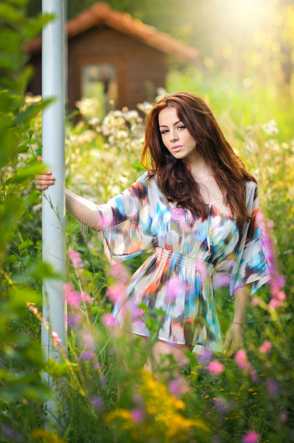 Young beautiful red hair woman in multicolored blouse in a sunny day. Portrait of attractive long hair female in nature royalty free stock image