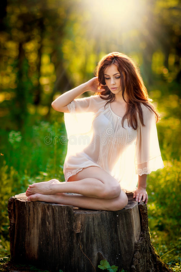 Young beautiful red hair woman wearing a transparent white blouse posing on a stump in a green forest. Fashionable girl. Young beautiful red hair woman wearing a stock photos