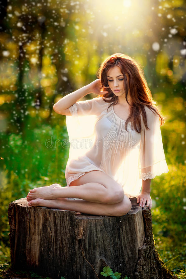 Young beautiful red hair woman wearing a transparent white blouse posing on a stump in a green forest. Fashionable girl stock photo