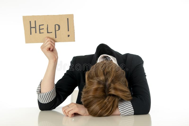 Beautiful young business woman overwhelmed and desperate holding a help sign stock image