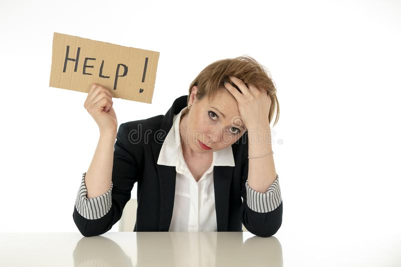Beautiful young business woman overwhelmed and tired holding a help sign royalty free stock images