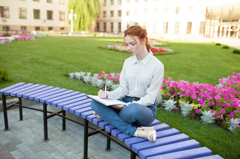 Young beautiful red-haired girl with freckles sitting on a bench near the university writing in a notebook with homework. Portrait of a student. Back to school stock photo