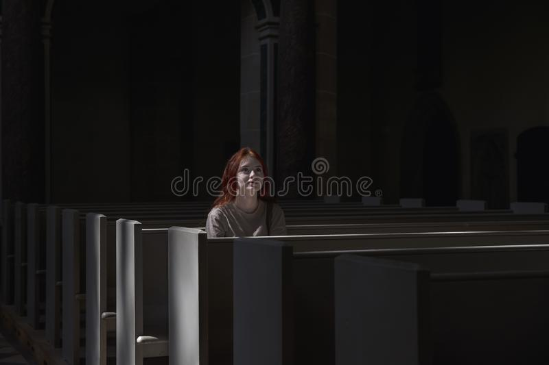 Young beautiful red-haired girl lonely sits in church praying to royalty free stock images