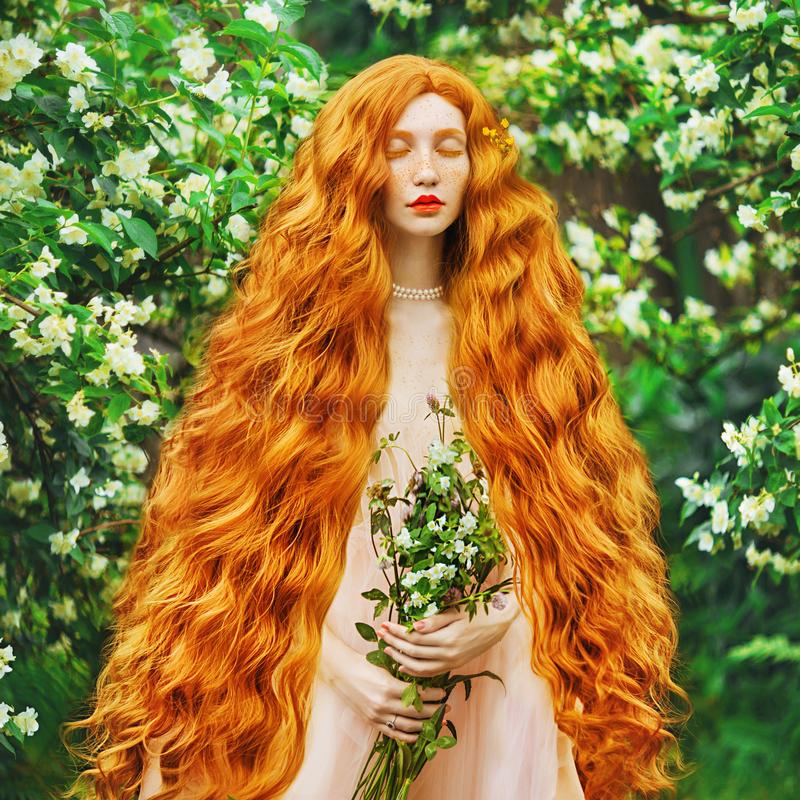 Young beautiful red-haired girl with very long curly hair with freckles on her face. Fabulous model with freckles against the background of a blooming spring royalty free stock photos
