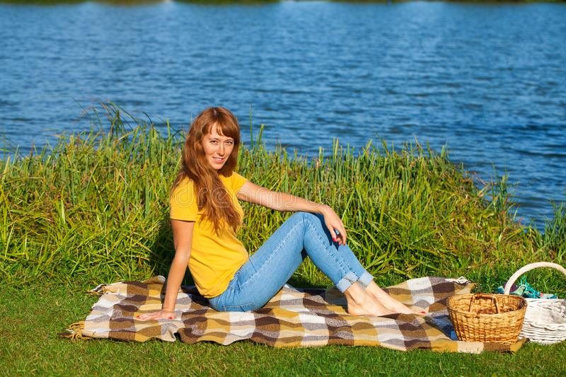 Young red-haired woman resting on the lawn near the lake. Young beautiful red-haired woman resting on the lawn near the lake stock image