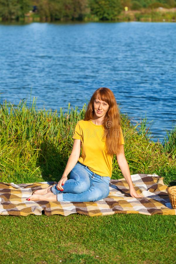 Young red-haired woman resting on the lawn near the lake. Young beautiful red-haired woman resting on the lawn near the lake royalty free stock images