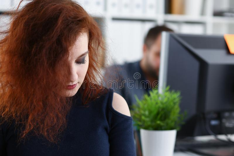 Young beautiful red haired woman sit at table in office in cabinet of her boss royalty free stock images