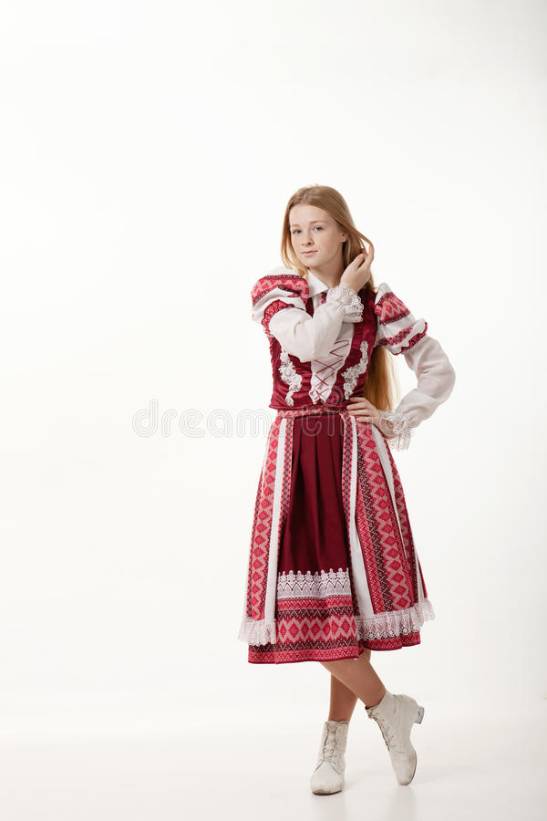 Young beautiful redhead folk dancer woman with gorgeous long hair in traditional authentic folk costume posing isolated on white stock photos