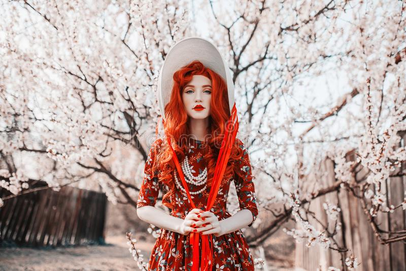 Young beautiful redhead girl with onspring flower background. Woman with pale skin and long red hair in retro dress. Blooming royalty free stock photography